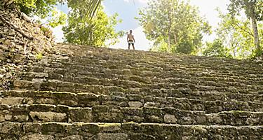 Man atop the steps of Chacchoben Mayan Ruins in Costa Maya, Mexico
