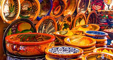 Mexican pottery in bold earthy colors and patterns at artisan market in Puerto Vallarta, Mexico