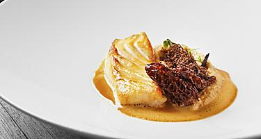 A roasted fillet of halibut and potato puree in a white bowl