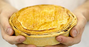 A chef holding a pie