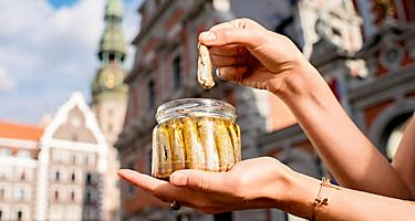A female holding a jar of sprats