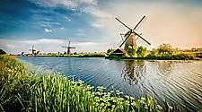 A several large windmills on a river in the Netherlands