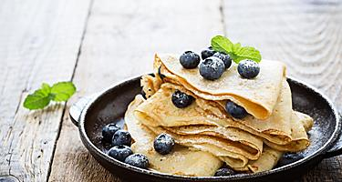 Homemade crepes served with fresh blueberries and powdered sugar on a cast iron skilled, from an eatery in Saguenay, Quebec