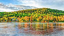 Chicoutimi river with riverfront houses and forest during sunset, in Saguenay, Quebec