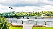 Sidewalk terrace with wooden boardwalk on a city park in downtown Saguenay, Quebec, with fjord river and bridge in the background