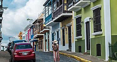 Woman walking through streets of Old San Juan surrounded by colorful architecture