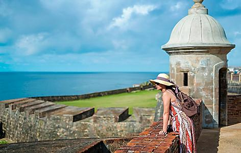 Woman leaning on fort El Morro to enjoy the view in San Juan, Puerto Rico