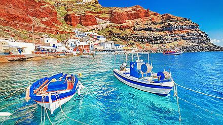 Beautiful landscape of two fishing boats anchored in blue water at the old port in Oia, Santorini, Greece