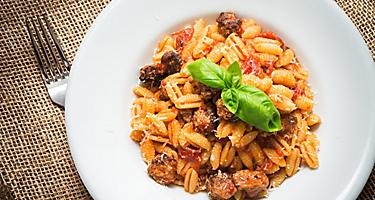 Pasta with tomato sauce and sausage on a white plate