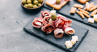 A tapas plate with serrano ham, cheese, and olives
