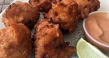 Seven conch fritters on a white plate with a lime wedge and aioli