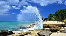 Wave crashing against rocks on a sunny day in Frederiksted Beach, St. Croix, U.S. Virgin Islands