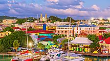 Catamarans docked near colorful architecture with Baroque Cathedral in the distance, St. John's, Antigua
