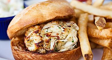 A crab cake sandwich with a side of french fries and cole slaw