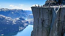 Side view of people standing on Cliff Preikestolen at the Lysefjord in Norway