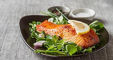 A baked salmon fillet with a side salad on a black plate