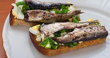 A herring sandwich on a white plate