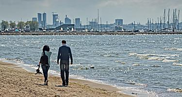 A man and a woman walking on a beach in Tallinn, Estonia