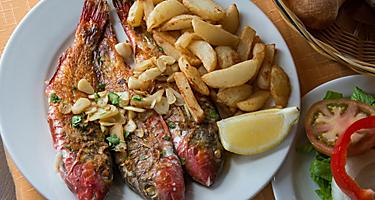 Three whole grilled fish with potatoes and salad on a white plate
