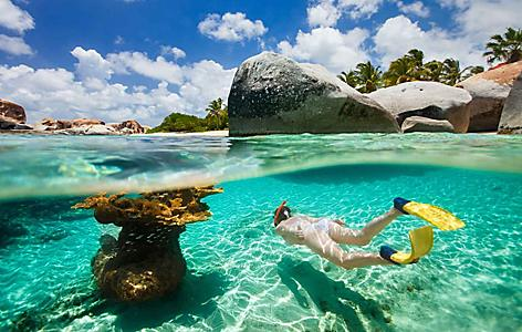 Girl snorkeling underwater through the rocks in Tortola, British Virgin Island