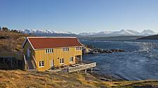A yellow waterfront building with a red roof near Tromso, Norway