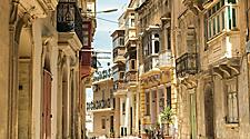Narrow street with traditional balconies in Valletta, Malta