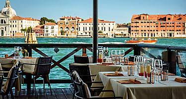 Tables set up at a waterfront café in Venice, Italy