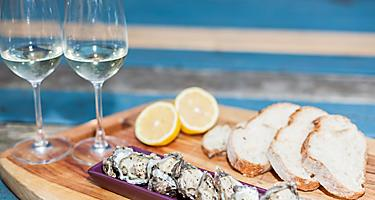 A platter with oysters with two glasses of wine, bread and a sliced lemon