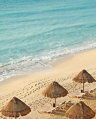 Malecon Beach with tanning chairs and tiki huts lined up along the shore in Yucatan, Mexico