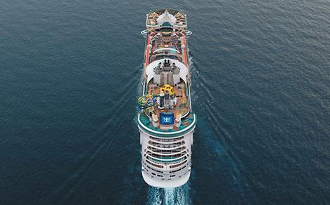 Drone shot aerial view of the cruise ship Independence of the Seas as it sails out straight into the sea