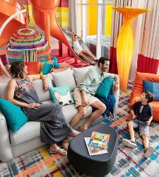 A family enjoying the Ultimate Family Suite while a girl goes down the slide
