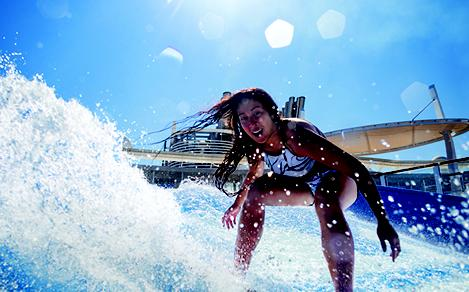 HM, Harmony of the Seas, Flow Rider, young woman riding surf, fun, waves, lens flare, action,