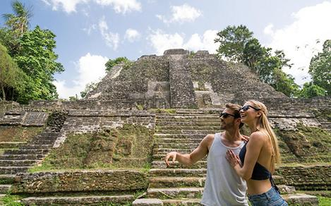 Couple taking a picture with Mayan Ruins in the Background