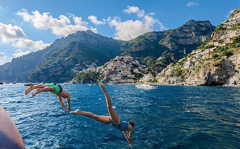 Italy Naples Positano Couple Jumping in Ocean