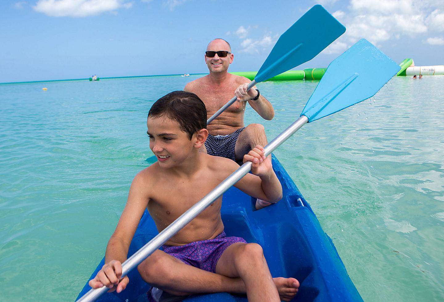 Father and Son Kayaking Through the Ocean