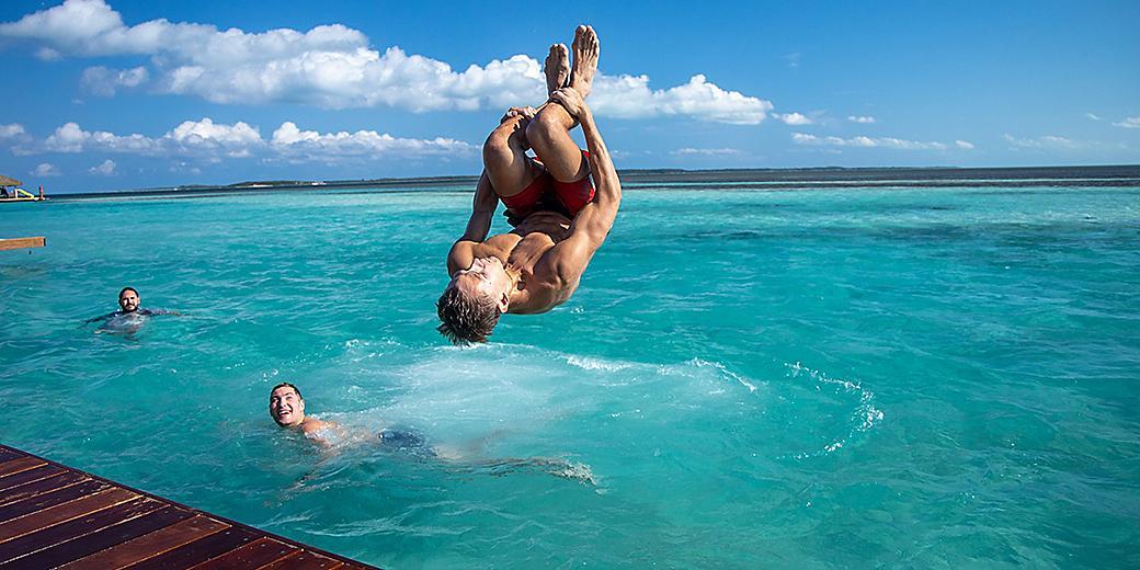 Coco Beach Club Man Jumping off Floating Cabana