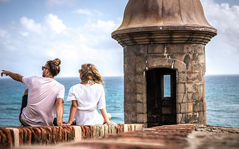 Couple Sitting on Top of Historical Fort