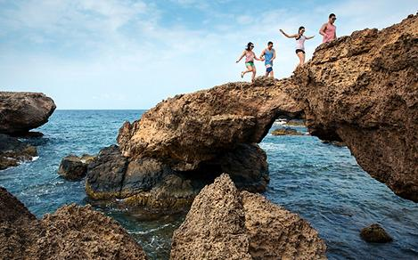 Family Jumping Through Rocks, Oranjestad, Aruba