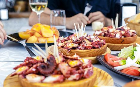 spain people eating pulpo gallega with potatoes