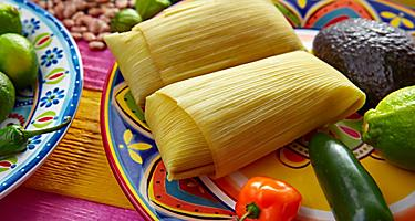 Two corn tamales on a colorful plate