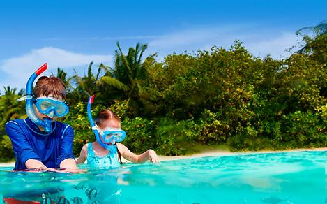Kids snorkeling on the beach at Kings Wharf, Bermuda. Top destination for a tropical family sailing cruise vacation.