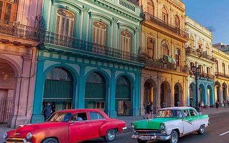 Vintage cars driving past buildings in Havana, Cuba. Royal Caribbean Cuba cruises from Miami, FL.
