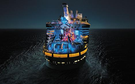 HM, Harmony of the Seas, night, nighttime drone shot, aerial of ship, aft, wide rear view, colorful lights, Ultimate Abyss in center, top pool decks, night sky, ocean in background,
